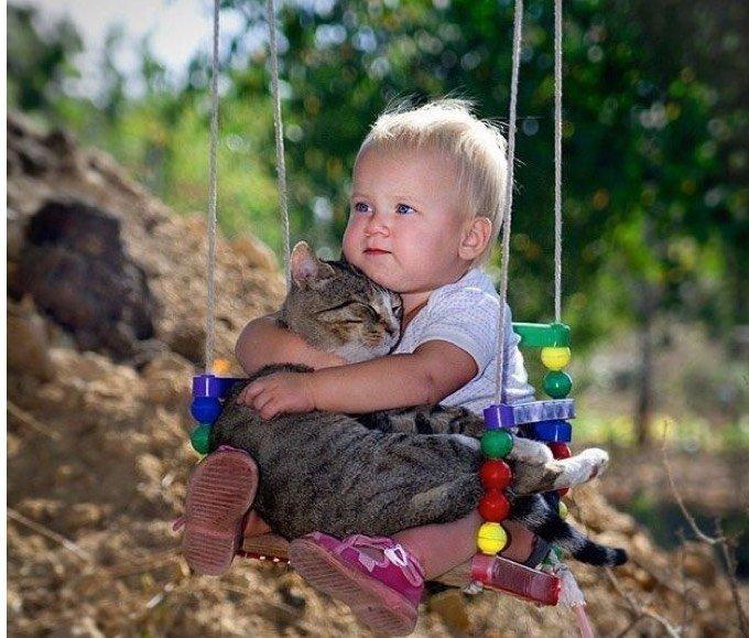 Bébé sur la balançoire avec son chat