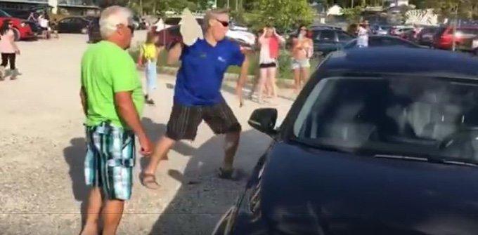 un homme sauve un chien d'une voiture au soleil